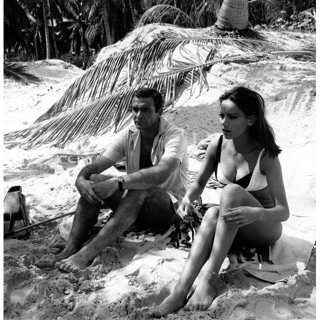 Film still of Sean Connery and Claudine Auger sitting on the sand in Thunde